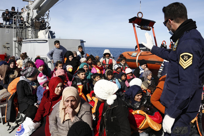 Офицер греческой миграционной службы разговаривает с мигрантами после проведенной спасательной операции в открытом море между турецкой границей и греческим островом Лесбос, 8 февраля 2016.