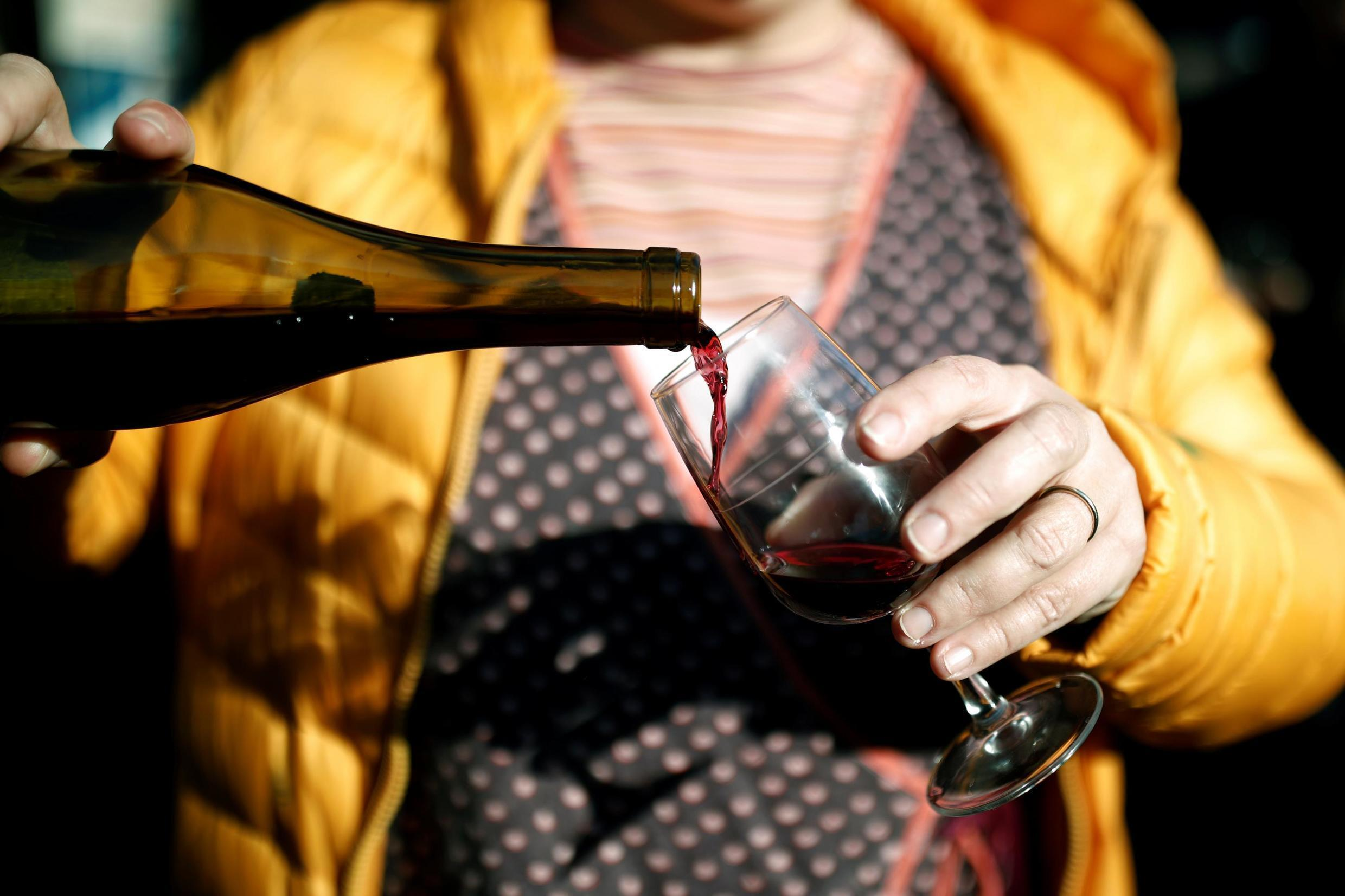 A woman pours a glass of Beaujolais Nouveau wine in a bistrot in Paris, France, November 21, 2019.