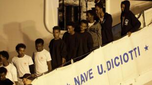 Migrantes a bordo do navio Diciotti desembarcam no porto de Catânia, na Sicília, neste domingo (26).
