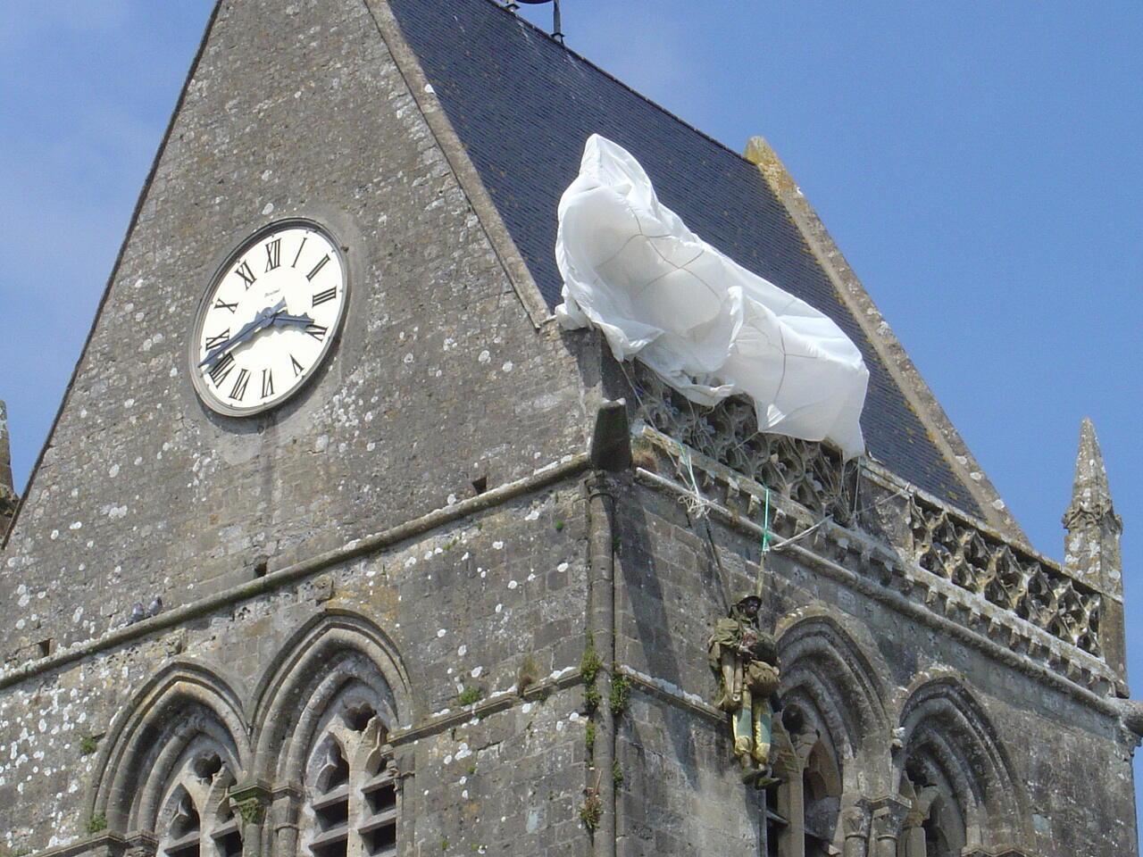 До сих пор на крыше церкви в Сент-Мер-Эглиз развевается парашют американского десантника в память о событиях ночи с 5 на 6 июня 1944 года