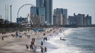 Les gens marchent et se rassemblent le long de la plage le matin du 23 mai 2020 à Myrtle Beach, Caroline du Sud. Les entreprises, y compris les divertissements, ont rouvert pour le week-end du Memorial Day.