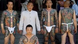 Yakuza members adopt elaborate tattoos - here some show them off at the Sanja Matsuri festival in Tokyo