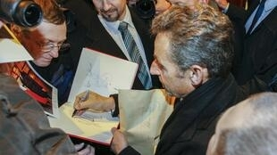 Nicolas Sarkozy signs autographs as he arrives to attend his wife's Carla Bruni-Sarkozy's concert in Lyon, 23 January 2014