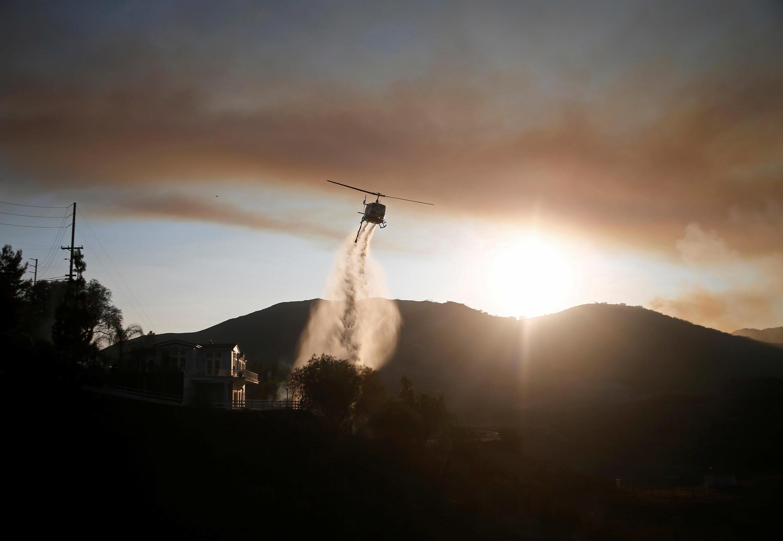 Un helicóptero tirando agua para combatir el incendio Woolsey, en la zona residencial de Malibú, California, el 10 de noviembre, 2018.