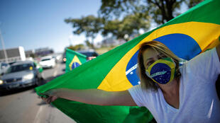 A supporter of far-right Brazilian President Jair Bolsonaro takes part in a protest during a motorcade against the president of the Chamber of Deputies Rodrigo Maia, quarantine and social distancing measures, amid the coronavirus disease (COVID-19) outbreak, in Brasilia, Brazil May 3, 2020.