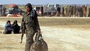 Une combattante de la milice kurde des Unités de protection de la femme (YPJ, qui fait partie des FDS), près de Syriens qui fuient les combats contre le groupe EI à Barghouz, le 12 février 2019.