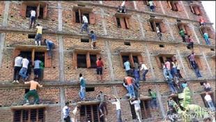 Triche scolaire : ces images montrent des dizaines de personnes armées de téléphones portables et d'antisèches accrochées aux fenêtres d'un immeuble de quatre étages, dans l'Etat du Bihar (Inde). Photo datée du 20 mars 2015.