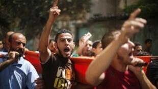 Des Palestiniens crient des slogans durant les funérailles de trois adolescents, tués durant l'offensive terrestre israélienne, à Gaza, le 18 juillet 2014.