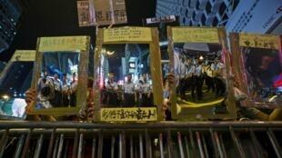 """香港佔中示威者舉起鏡框底部寫着""""我們不是敵人""""的大鏡子映射守衛鐵柵欄的警察"""