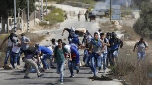 Vijana wa Kipalestina wakiwarushia mawe askari polisi wa Israel , wakijaribu kuingi katika mji wa Bet El, karibu na mji wa Ramallah, Oktoba 5 2015.