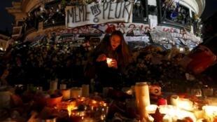 """Девушка зажигает свечу на площади Республики под плакатом """"Не боимся"""" после пятничных терактов в Париже. Франция, 22 ноября, 2015"""