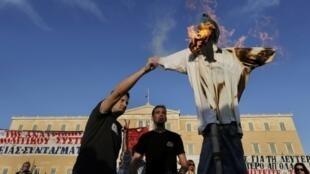 Diante do Parlamento grego, manifestantes encendeiam boneco representando trabalhador