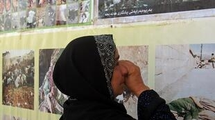 A woman looks at a memorial for the Halabja victims