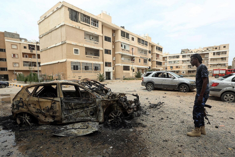 Un combattant du GAN devant la carcasse d'une voiture dans les faubourgs de Tripoli le 9 mai 2020 (image d'illustration).