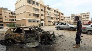 Un combattant du GNA (Gouvernement d'union nationale) devant la carcasse d'une voiture dans les faubourgs de Tripoli le 9 mai 2020. (Image d'illustration)