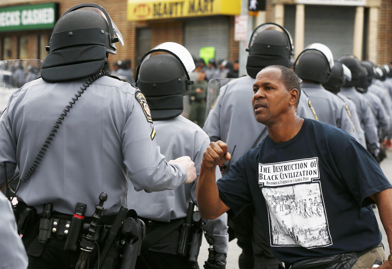 Un homme lève son poing envers les policiers après l'annonce de la poursuite de 6 d'entre eux. Baltimore, le 1er mai 2015.