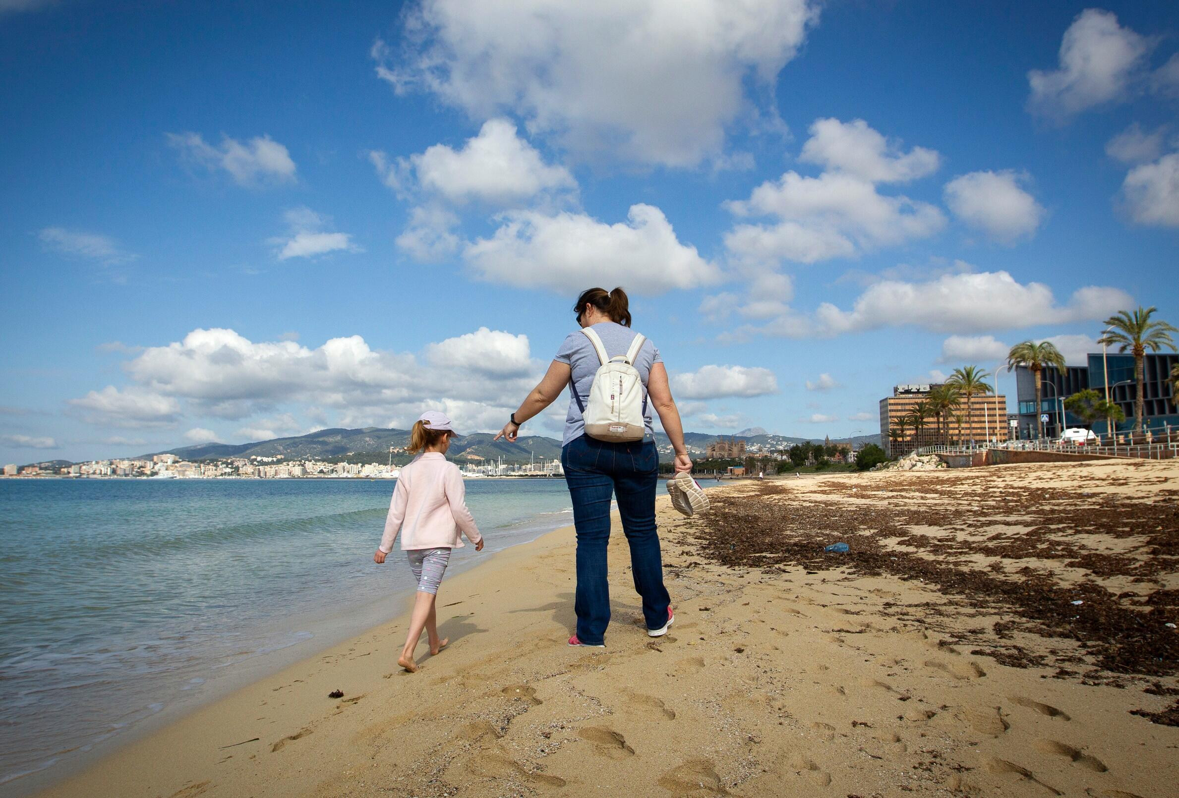 Mother and child on deserted beach of Spain's Palma de Mallorca, on 26 April, where many German tourists own property.
