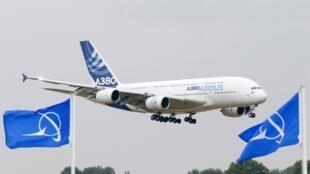 Un Airbus A380 atterrit devant le salon du Bourget. Au premier plan, des drapeaux Boeing.