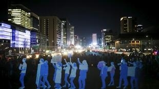 Amnesty International a fait défiler des hologrammes représentant des manifestants dans le centre de Séoul, le 24 février 2016.
