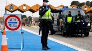 Una policía nacional española gesticula en un control instaurado junto al peaje de La Jonquera, en la frontera con Francia, el 17 de marzo de 2020 en la provincia catalana de Gerona