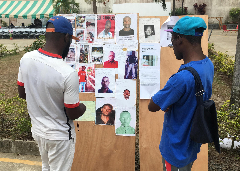 Des Gabonais devant un tableau sur lequel figure le signalement de personnes décédées ou disparues dans les violences post-électorales, le 19 septembre à Libreville.