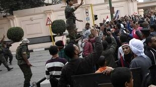 An Egyptian soldier tries to calm opposition supporters outside the Interior Ministry