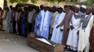 Ziguinchor, le 7 janvier 2018. Des hommes prient devant le cercueil d'un des jeunes 13 tués.