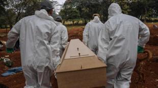 Trabajadores del cementerio de Vila Formosa, en las afueras de Sao Paulo, cargan el ataúd de una persona fallecida por COVID-19, el 20 de mayo de 2020