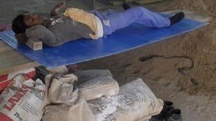 Operário dorme no chão em obra de estádio no Catar para o Mundial 2022.