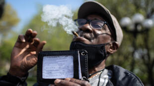 A man smokes a joint and shows his vaccination card as marijuana activists hand out free joints to vaccinated New Yorkers on April 20, 2021 in New York City