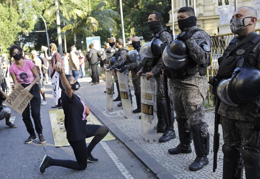 Uma mulher grita com policiais militares durante protesto contra crimes cometidos pela polícia contra negros nas favelas, fora do governo do estado do Rio de Janeiro, Brasil, domingo, 31 de maio de 2020.