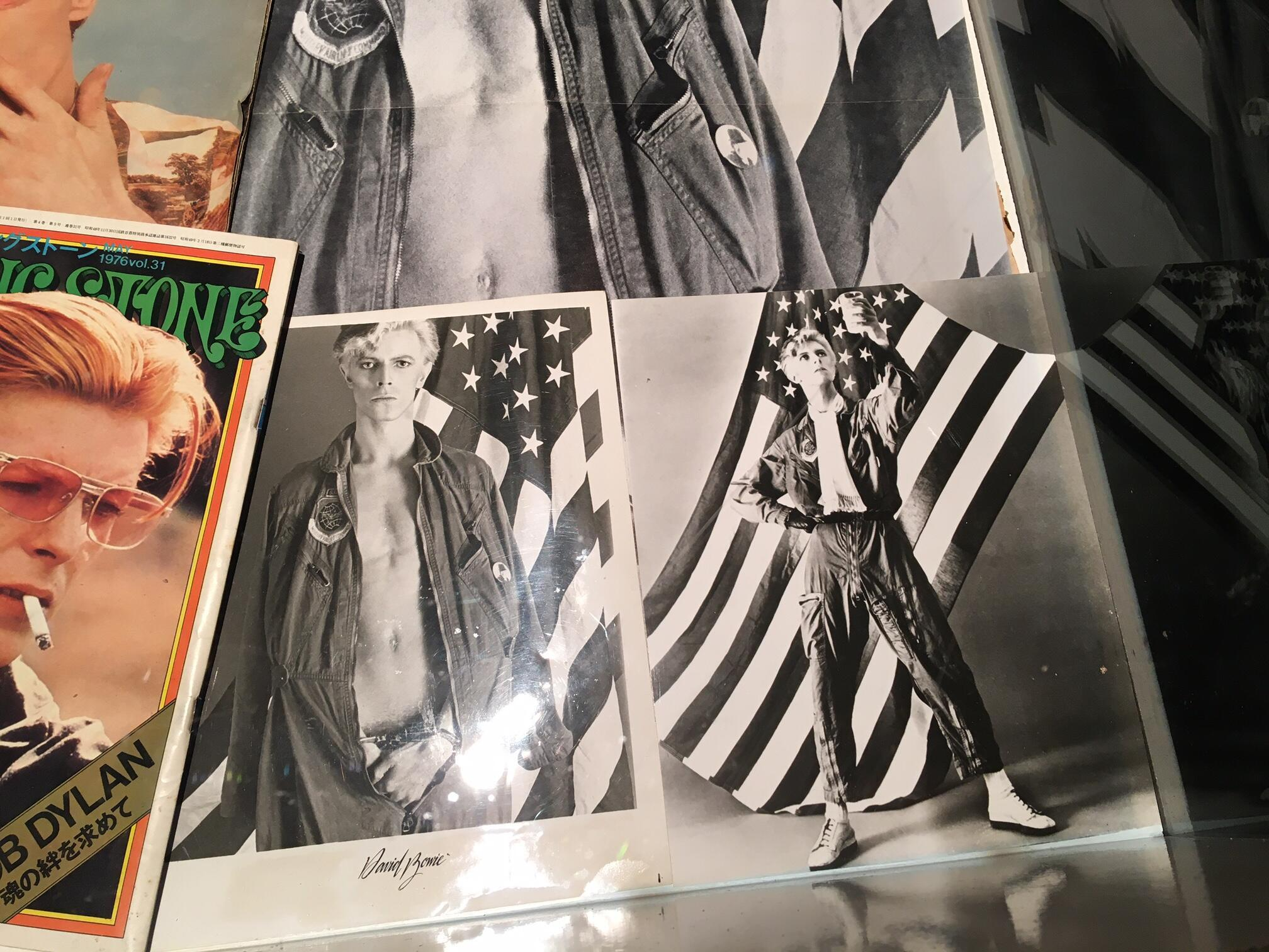 "The photo (L) with David Bowie posing in front of the US flag half naked with handcuffs was another version for the front cover of the ""Young Americans"" LP but it was censored like the one with the glass of milk (R)."