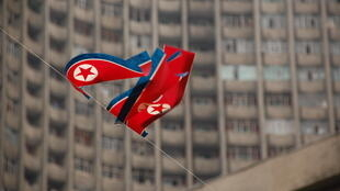 Bandeira norte-coreana em frente a um conjunto residencial em Pyongyang, foto ilustração