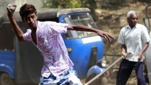Un partidario del presidente Rajapakse lanza una piedra contra manifestantes pro Fonseka, Colombo 10 de febrero de 2010