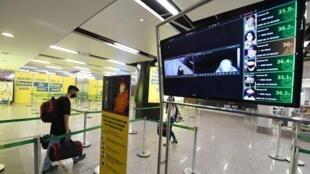 Un passager marche près d'un écran montrant la température du corps à l'aide d'une caméra de surveillance à l'aéroport de Brasilia, le 14 mai 2020.