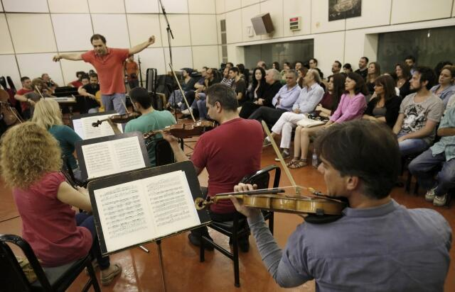 Musicians from ERT's symphony orchestra play the Greek national anthem during a continuing live broadcast at Greek state television ERT headquarters in Athens