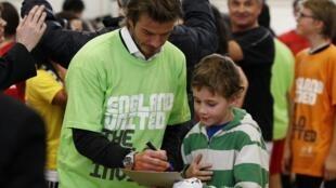 Footballer David Beckham, a key player in England's 2018 World Cup bid, signs autographs on a school visit