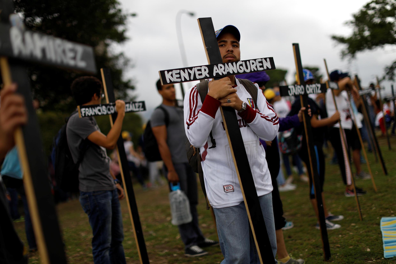 Opositores seguram cruzes com nomes de mortos durante manifestações contra o presidente venezuelano, Nicolas Maduro, em Caracas. 15 de maio de 2017.