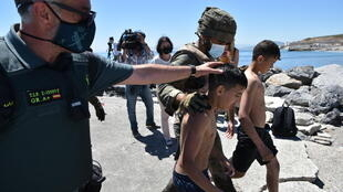 Soldados españoles y miembros de la Guardia Civil asisten a menores migrantes tras llegar a nado al enclave español de Ceuta, el 19 de mayo de 2021
