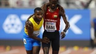 L'Arubais Jonathan Busby termine son 5.000m avec le soutien du Bissau-Guinéen Braima Suncar Dabo lors des Mondiaux d'athlétisme 2019.