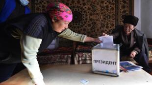 Una mujer deposita su papeleta en una urna durante una votación anticipada en vísperas de las presidenciales de Kirguistán en la aldea de Arashan, a unos 20 km de Biskek, el 9 de enero de 2021