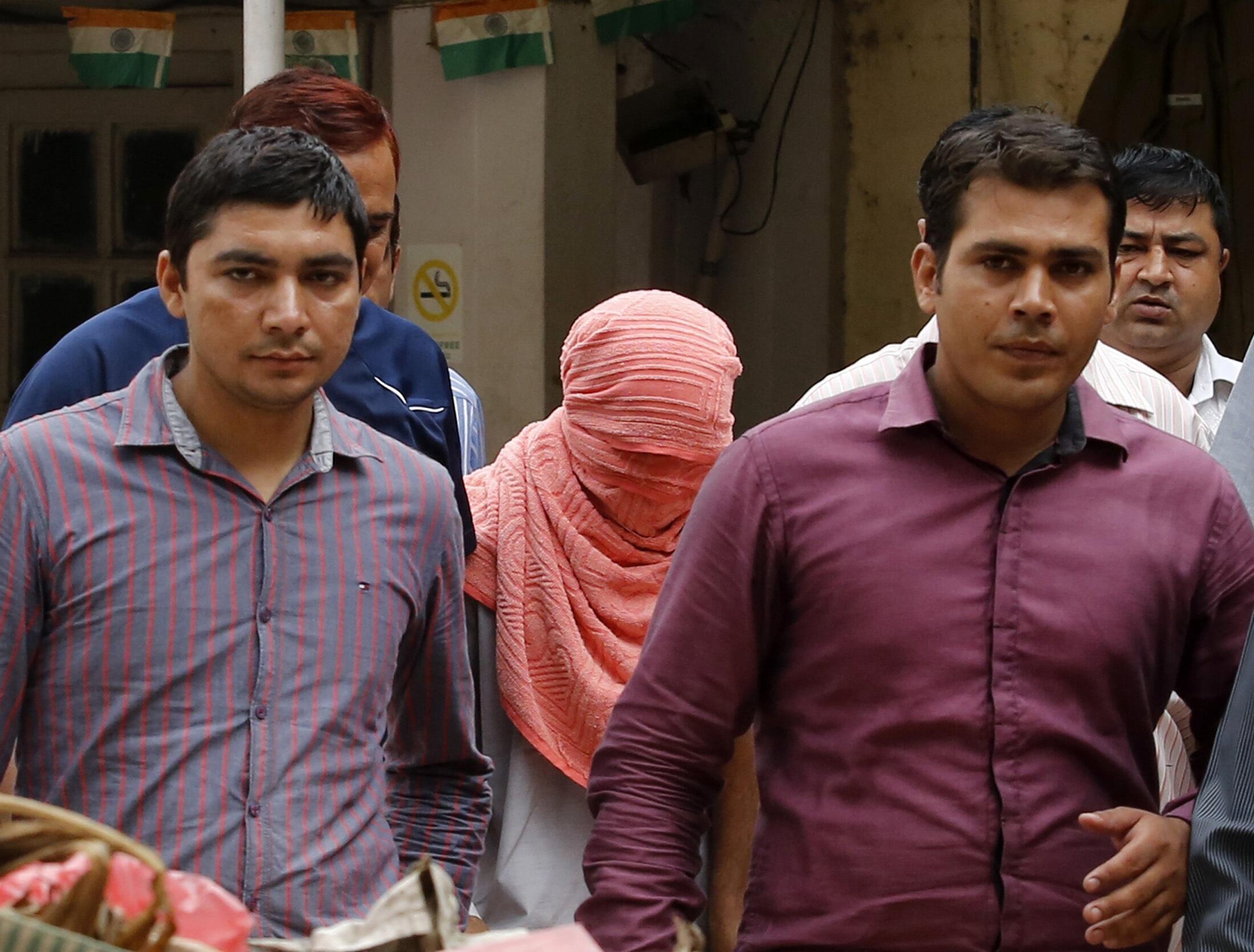 Le mineur comdamné (tête recouverte) sort escorté du tribunal, le 31 août à New Delhi.