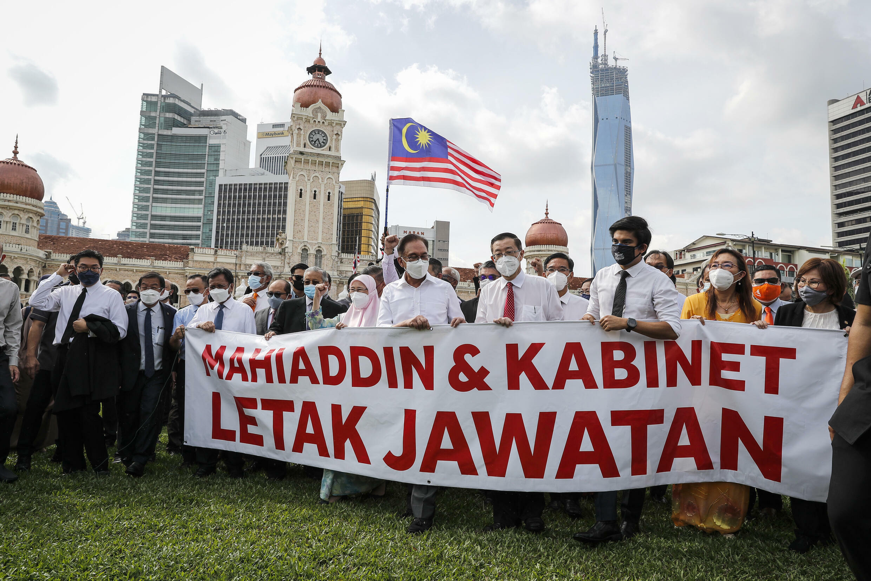 Les députés de l'opposition en marche vers le Parlement, dont l'accès a été protégé par un bouclier de policiers, réclament la démission du Premier ministre, à Kuala Lumpur, le 2 août 2021.