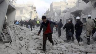 Les habitants du quartier de Tarek al-Bab, en banlieue d'Alep, circulent sur les ruines de leurs immeubles bombardés, le 18 décembre 2013.