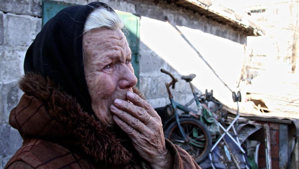 Galina pleure la perte de son mari, devant sa maison détruite par un obus. Elle n'a plus aucun revenu.