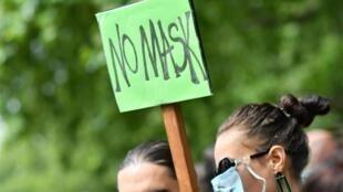 Une manifestante brandit une pancarte contre le port du masque lors d'une manifestation à Londres, le 19 juillet 2020.