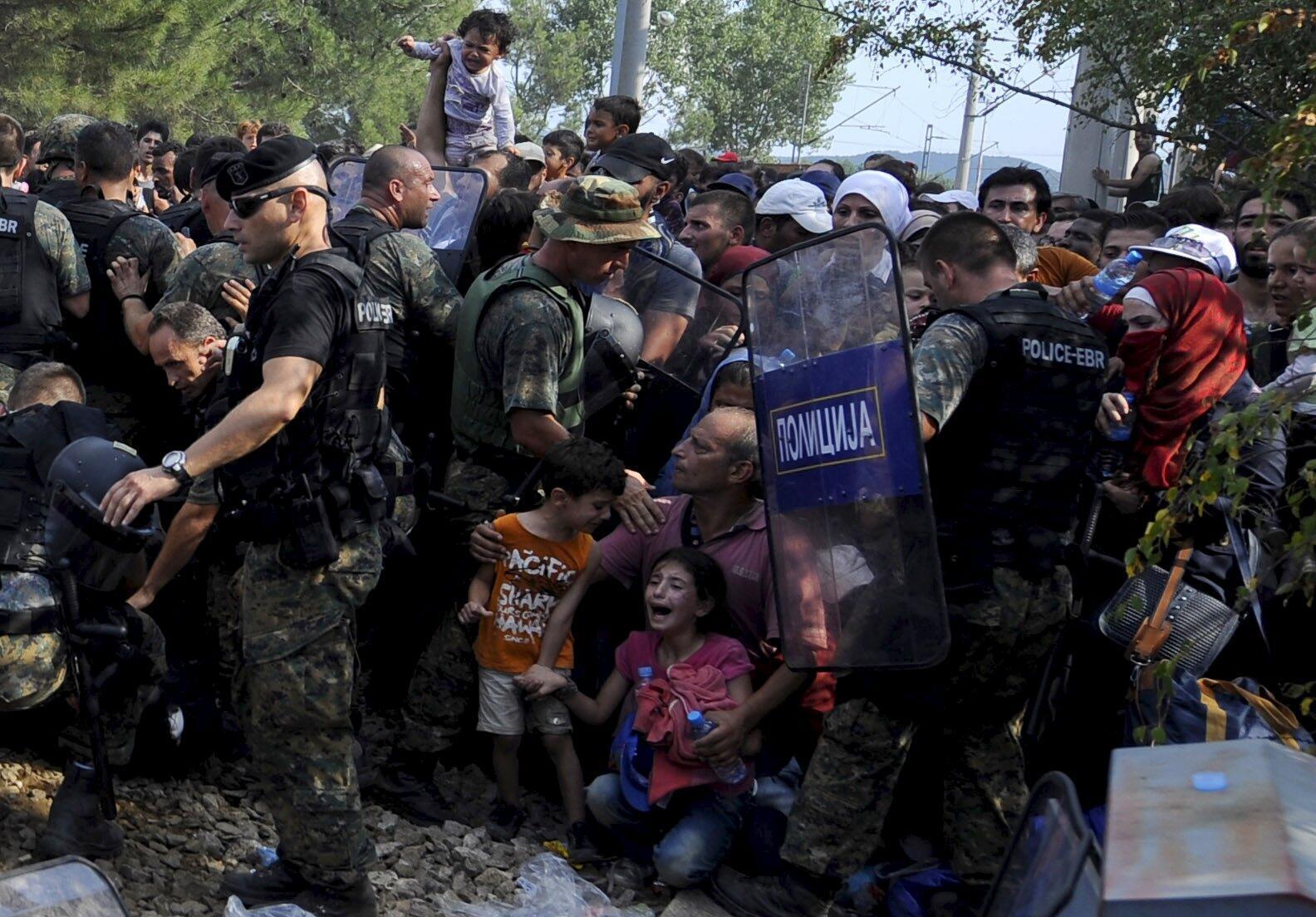 Người tỵ nạn Syria cầu xin các cảnh sát biên phòng Macedonia.