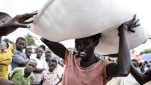 Une femme congolaise porte un sac de nourriture lors d'une distribution le 25 octobre 2017, à Kasala, dans la région du Kasaï, en RDC.