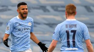Manchester City's Riyad Mahrez (L) celebrates scoring against Paris Saint-Germain