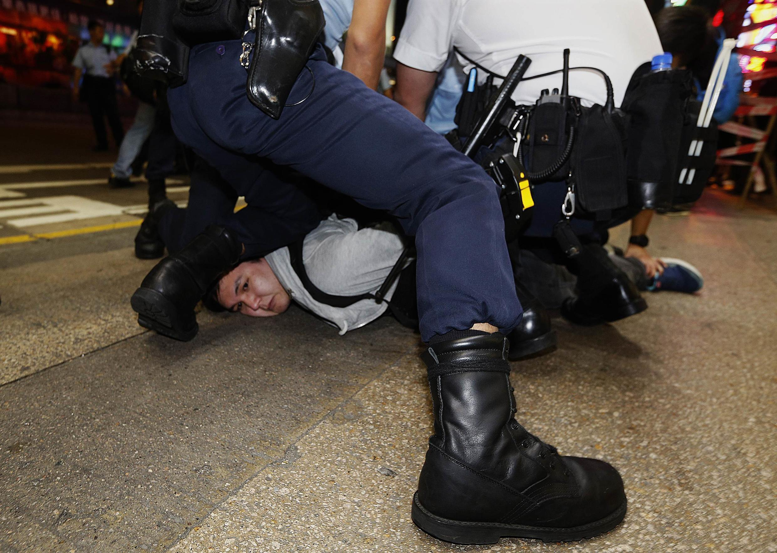 A protester is detained by the police during a confrontation at Mongkok shopping district in Hong Kong November 26, 2014.